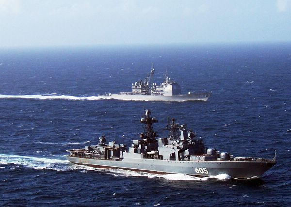 The Russian Federation Navy Udaloy-class guided missile destroyer RFNS Admiral Levchenko (DDG 605), foreground, and the guided missile cruiser USS Hue City (CG 66) maneuver alongside one another.