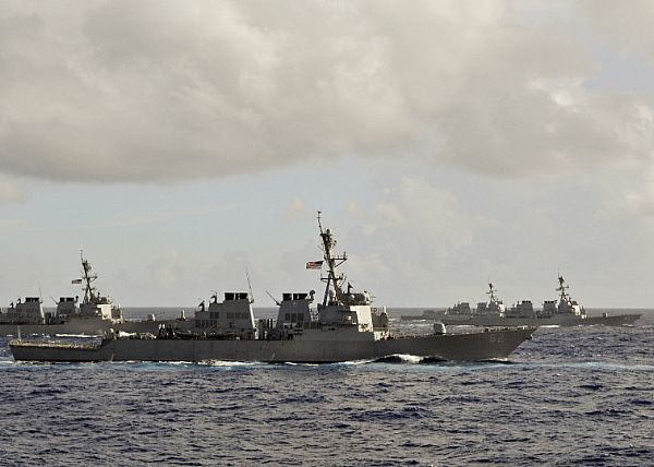 Four Arleigh Burke-class guided-missile destroyers underway in the Pacific Ocean.