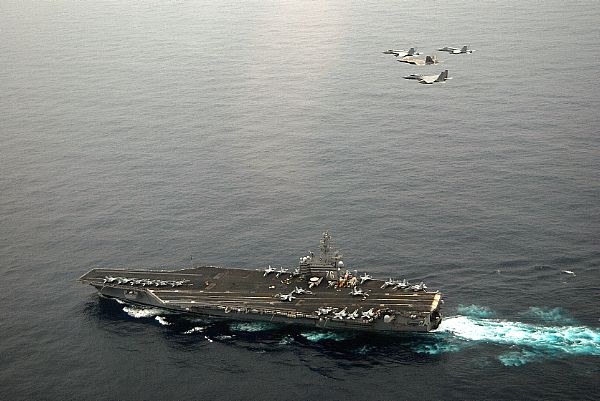 An F/A-18E Super Hornet, an F-22A Raptor, an F-15C Eagle, and an F/A-18C Hornet fly in formation above USS Ronald Reagan (CVN 76).