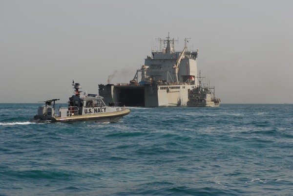 A US Navy force protection boat assigned to Maritime Expeditionary Security Squadron (MSRON) 5 provides port security for Landing Craft Utility Five Forks (LCU 2018) as it transfers equipment from the Royal Navy fleet auxiliary ship Cardigan Bay (L 3009) in the Persian Gulf.